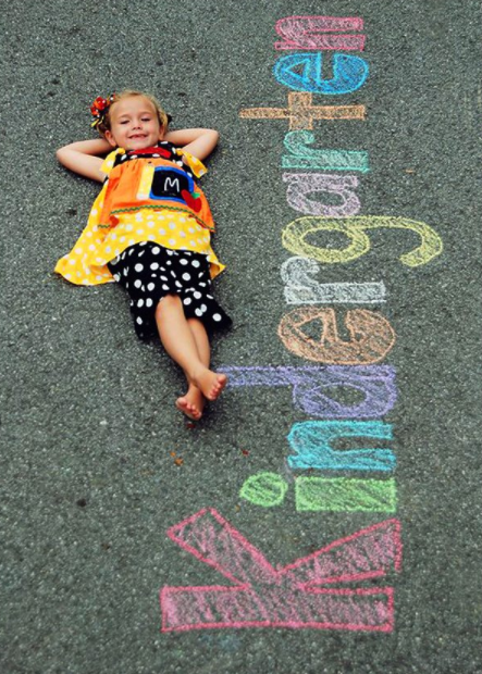 little girl laying on the driveway with Kindergarten written next to her