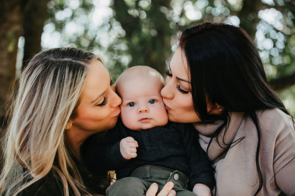 lesbian couple kissing their baby boy on the cheek