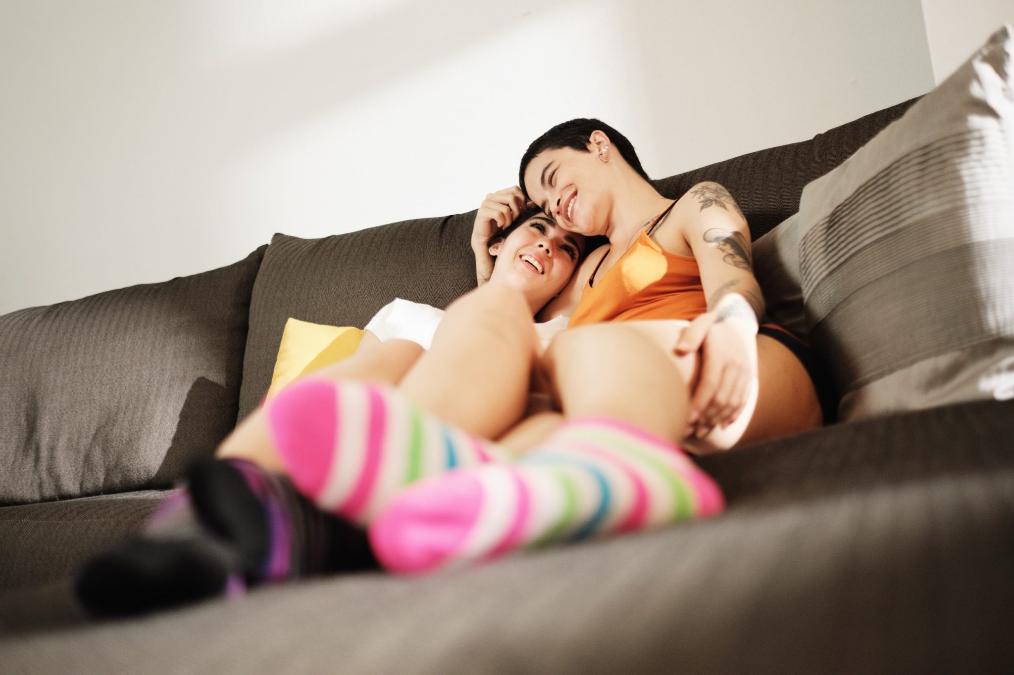 Lesbian Couple Kissing On Sofa In Living Room