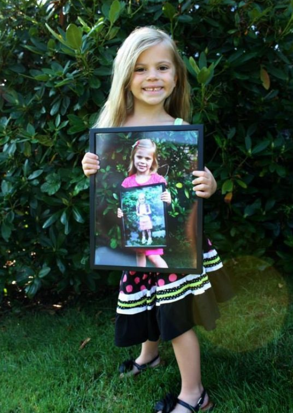 small girl holding up portraits of herself from every year of school