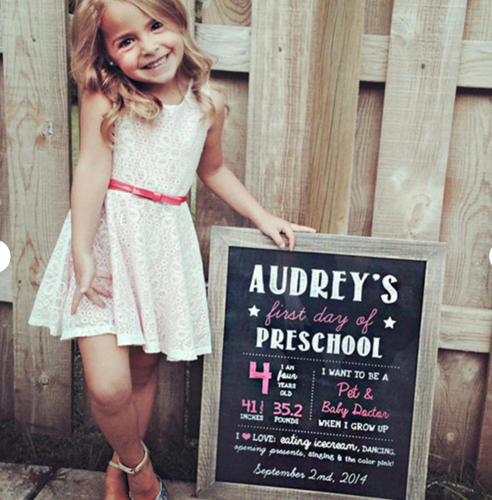 "little girl posing with a chalkboard saying ""first day of preschool"""